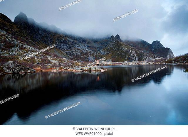 Norway, Lofoten Islands, Henningsvaer, man standing at seashore with raised arms
