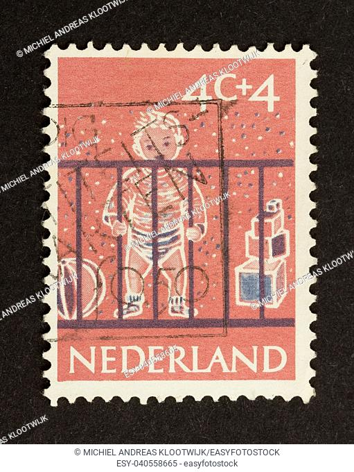 HOLLAND - CIRCA 1950: Stamp printed in the Netherlands shows a baby in a box, circa 1950