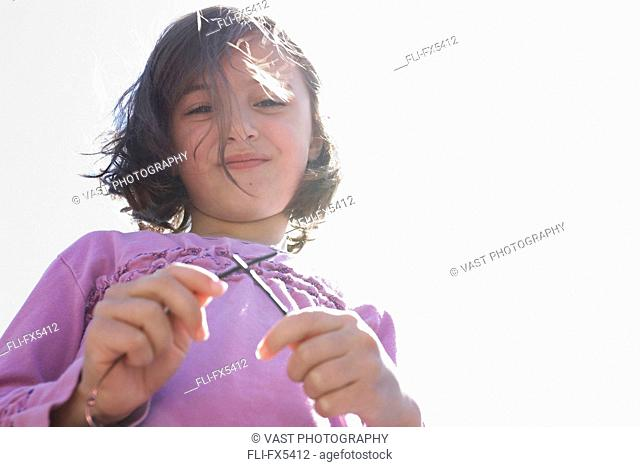 Young Girl Looking into Camera Holding Sunglasses, Toronto, Ontario
