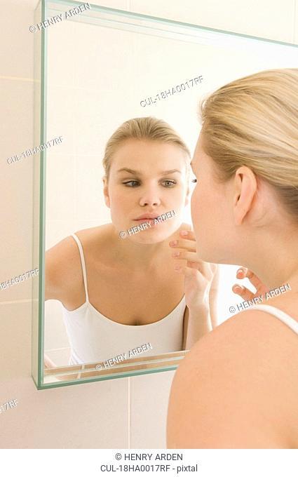 Female beauty inspecting skin in mirror