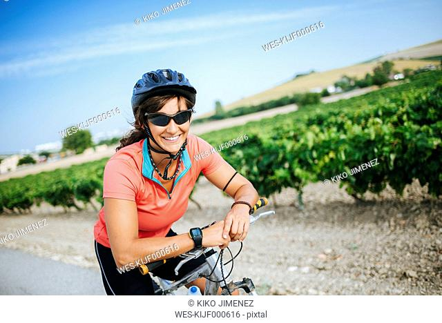 Spain, Andalusia, Jerez de la Frontera, Portrait of cyclist woman looking at camera while smiling