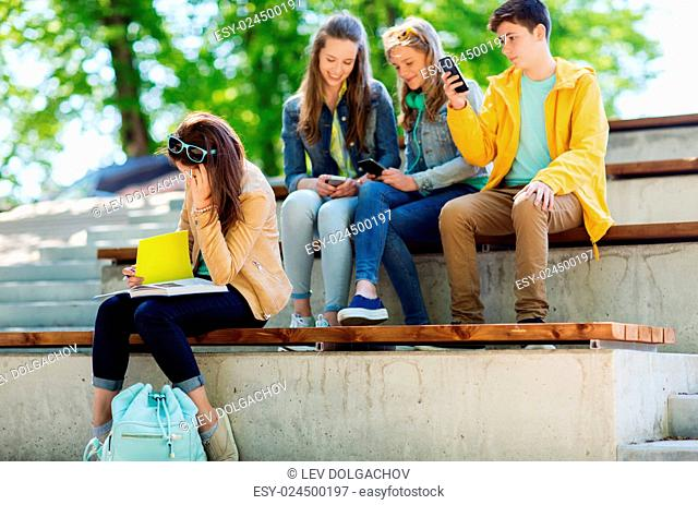 education, bullying, high school, social relations and people concept - unhappy student girl with book suffering of classmates mockery