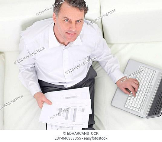view from the top.businessman working with documents sitting on sofa and looking at camera