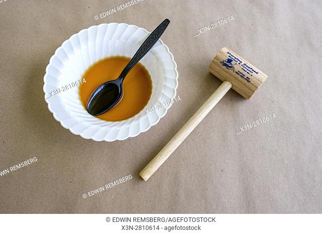 A helping of crab soup next to a crab mallet on a picnic table