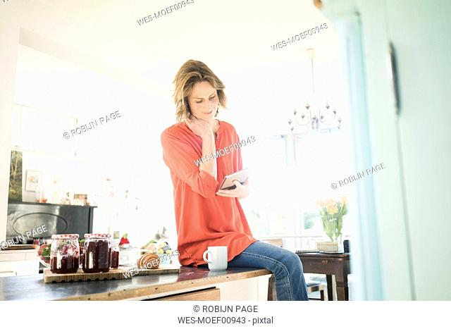 Woman with tablet and homemade strawberry jam at home