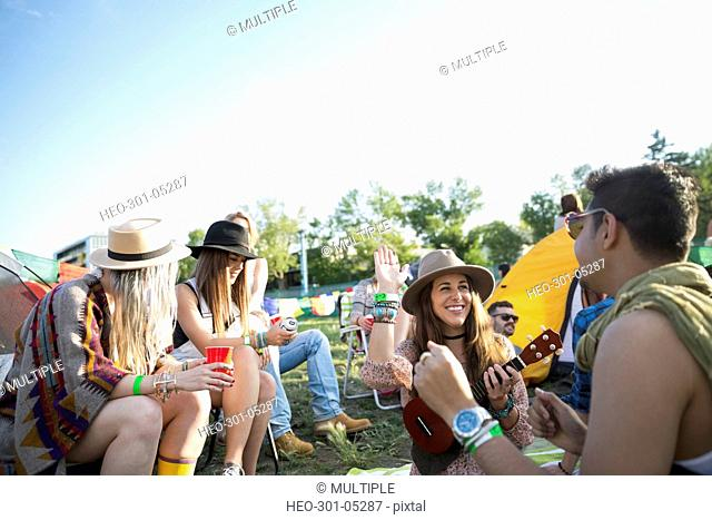 Young friends hanging out at summer music festival campsite
