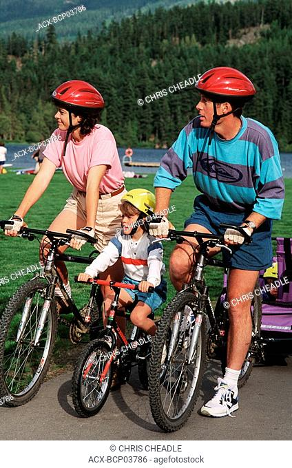 family cycles on paved trails rest at Rainbow Park, Whistler, British Columbia, Canada