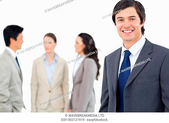 Smiling young businessman with talking associates behind him against a white background