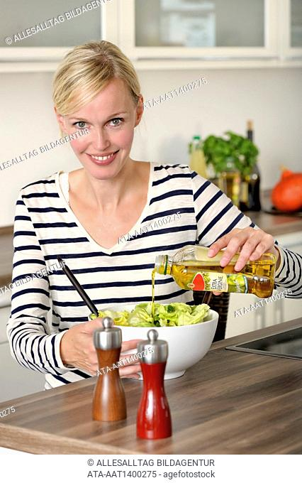 Woman is preparing salat with olive oil