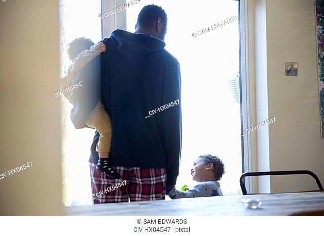 Father and sons in pajamas at window