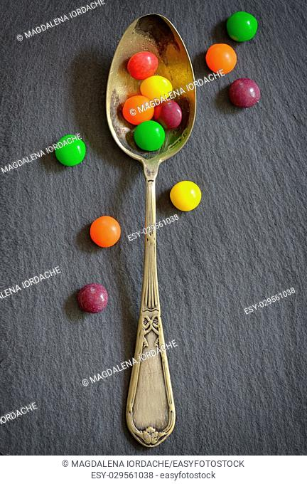 Colorful jelly candies in spoon on ardesia plate