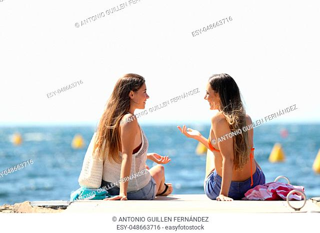 Two tourists on summer vacartions talking near the sea on the beach