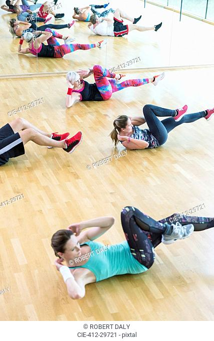 Exercise class doing bicycle sit-ups at gym
