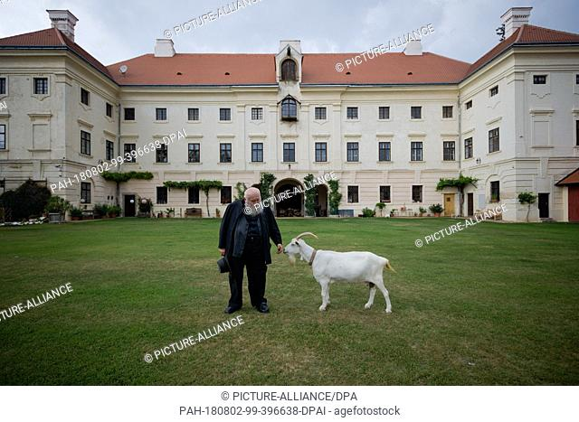 01 August 2018, Austria, Prinzendorf an der Zaya: The Austrian painter and action artist Hermann Nitsch stands in front of his castle next to a goat