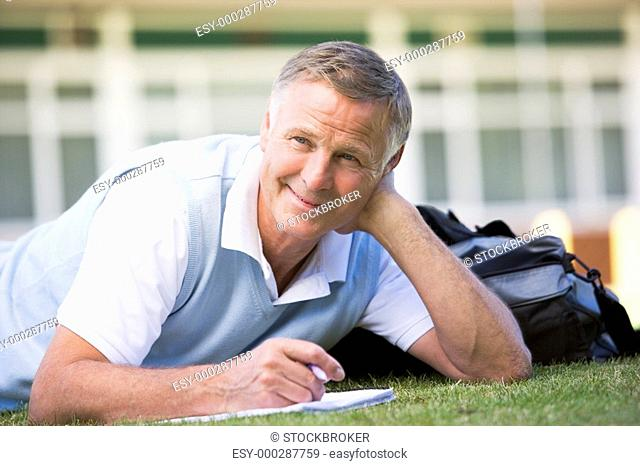 Adult student lying on lawn of school with notebook