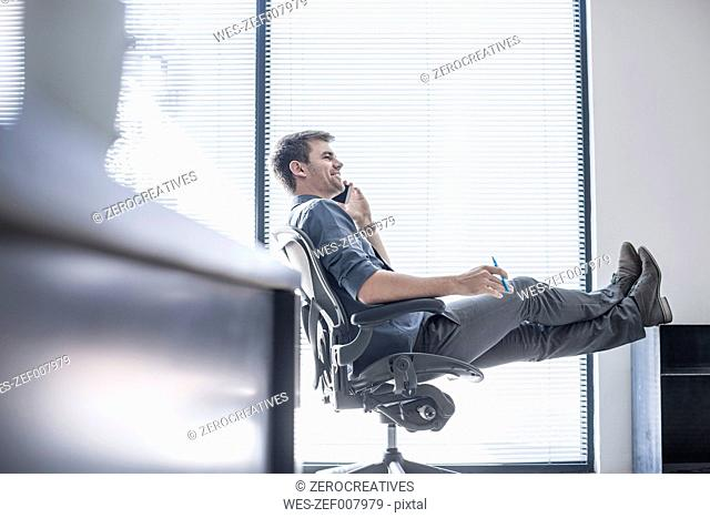 Businessman in office on the phone with feet up