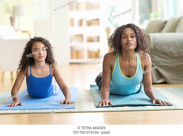 Mother and daughter (8-9) exercising in living room