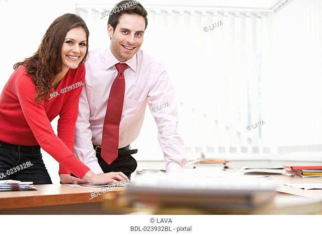 portrait of young businesswoman and male colleague sitting at desk