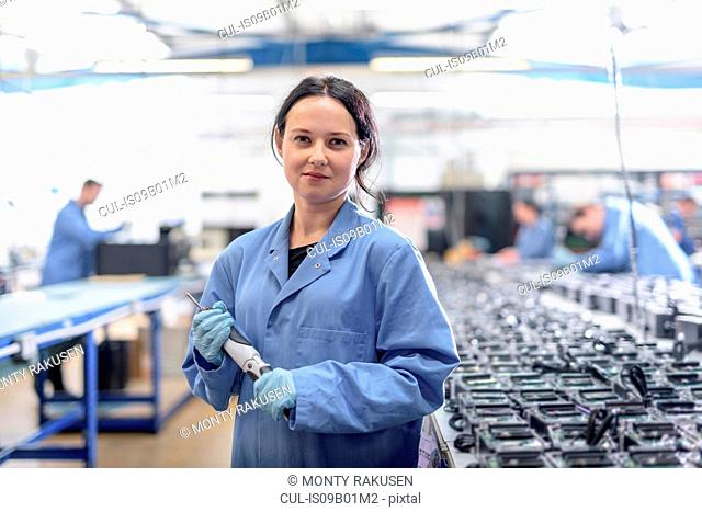 Portrait of female worker in circuit board assembly factory