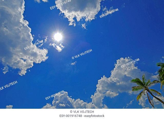 Sun in blue sky shining on beach of Mahahual in Mexico