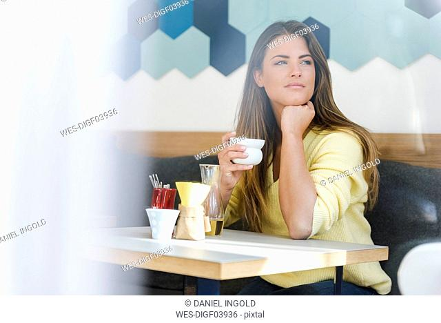 Young woman in a cafe holding cup of coffee