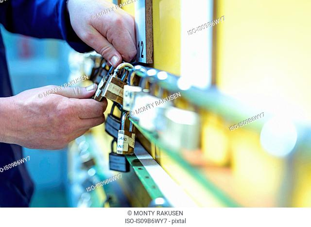 Cropped view of locomotive engineer inspecting safety padlocks in train works