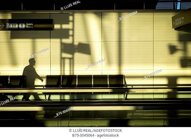 Silhouette of an unrecognizable executive walking through the airport terminal of Aeropuerto de Madrid-Barajas Adolfo Suárez. Madrid, Spain, Europe