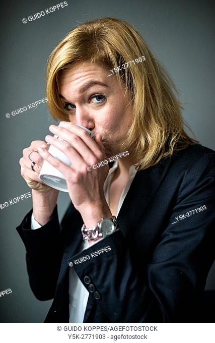 Tilburg, Netherlands. Young adult caucasian business woman drinking a large cup of tea