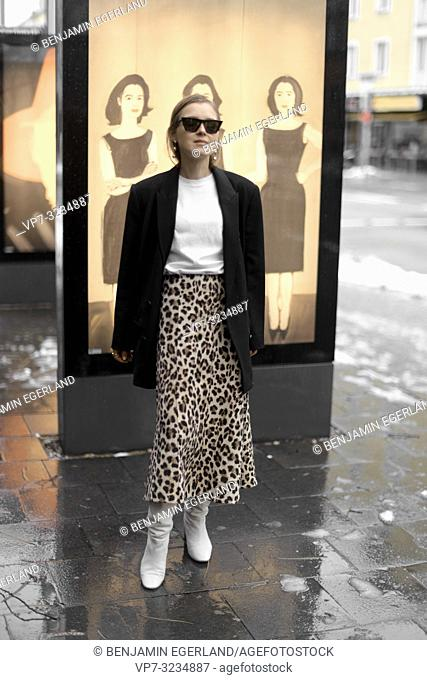 fashionable woman standing in front of Alex Katz art pictures at street, in Munich, Germany