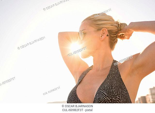 Sunlit portrait of woman tying hair in bun at beach, Alicante, Spain