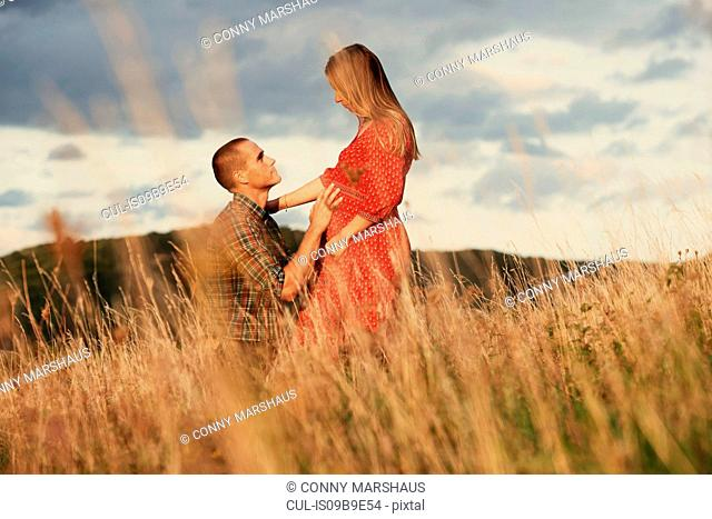 Mid adult man kneeling with hand on pregnant wife's stomach in field