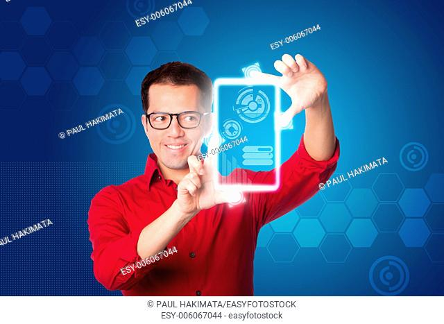 Happy smiling Business man in red shirt looking at digital graph chart on hologram touch screen computer tablet device, on blue