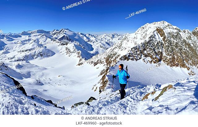 Femal back-country skier ascending to Agglsspitze, mountain scenery in background, Pflersch valley, Stubai Alps, South Tyrol, It