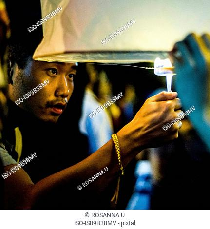 Young man lighting paper lantern for Loy Krathong Paper Lantern Festival in Chiang Mai, Thailand