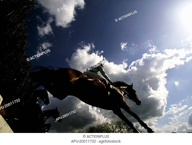 Horses jumping over a fence during a race