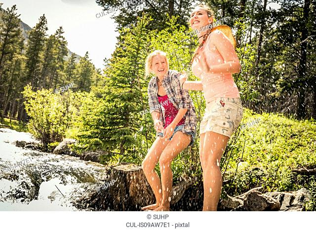 Young woman and teenage girl splashing in forest river, Red Lodge, Montana, USA