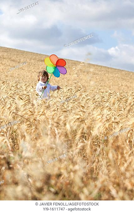 child with a pinwheel in the field