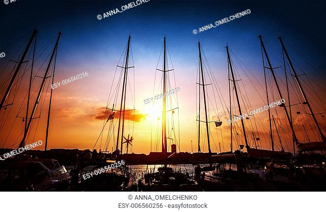 Sailboats mast on beautiful sunset background, harbour for sail yacht in the night, old marina in European city, travel and tourism concept