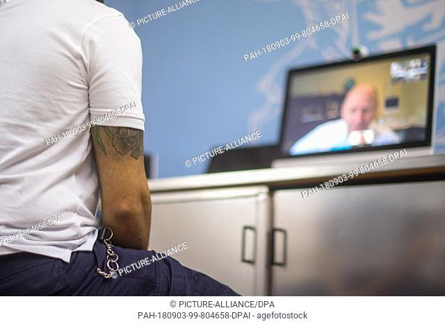 03.09.2018, Baden-Württemberg, Stuttgart: An employee of the correctional facility sits in front of the computer terminal belonging to the project during the...