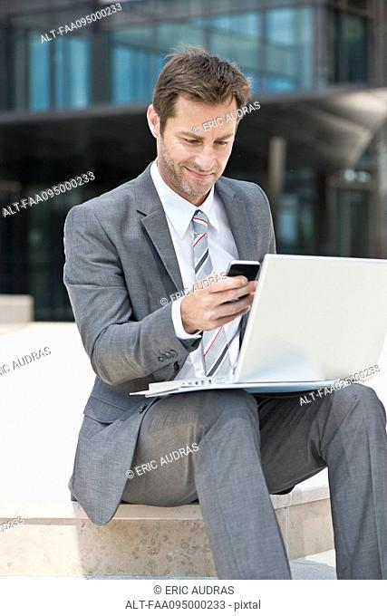 Businessman multitasking while working outdoors