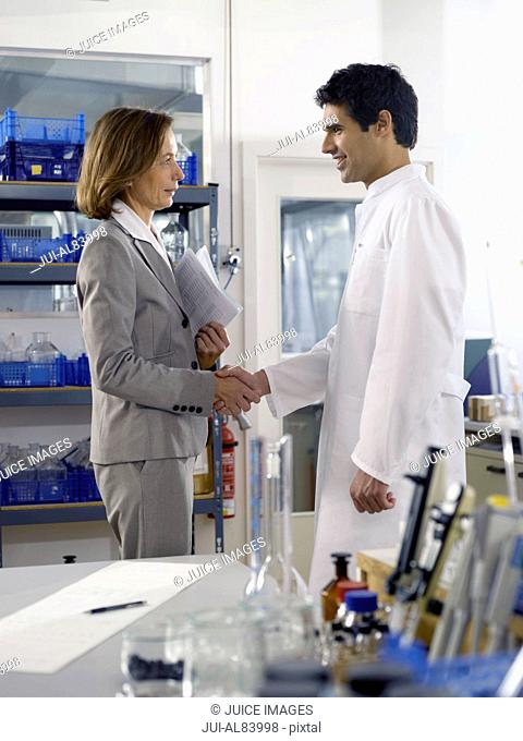 Businesswoman and scientist shaking hands in laboratory