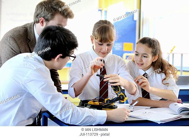 Teacher teaching high school students assembling robot in science class