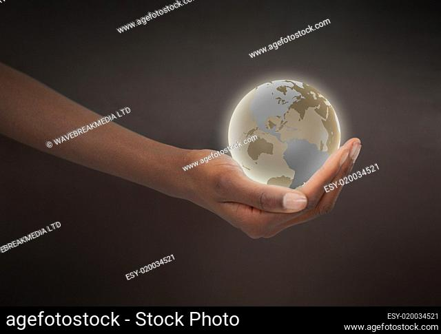 Feminine hand holding a glowing planet globe