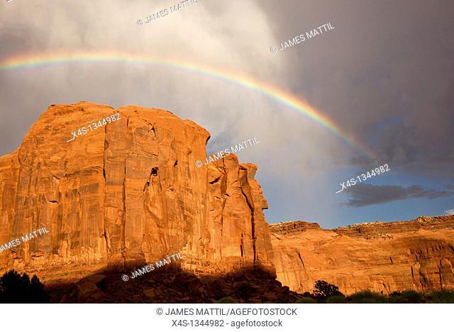 Rainbow arches above massive sandstone cliffs