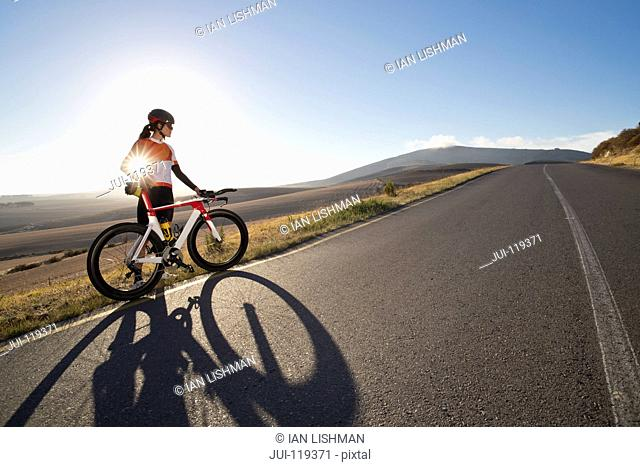Female cyclist with race bicycle on sunny open road
