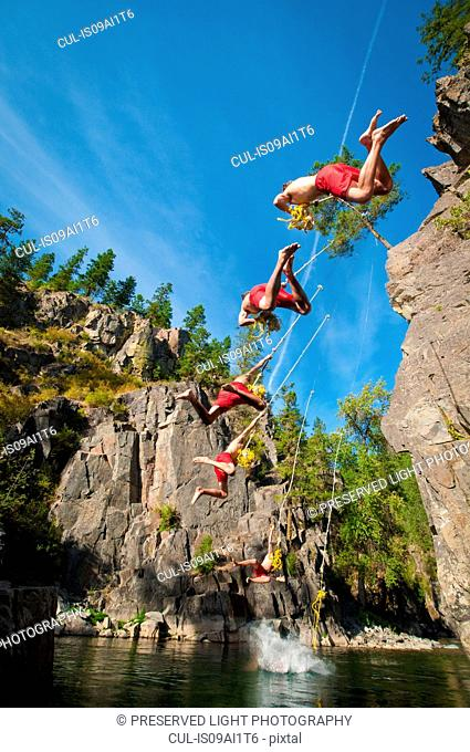 Young man on rope swing and falling into the Goat River near Creston, British Columbia, Canada