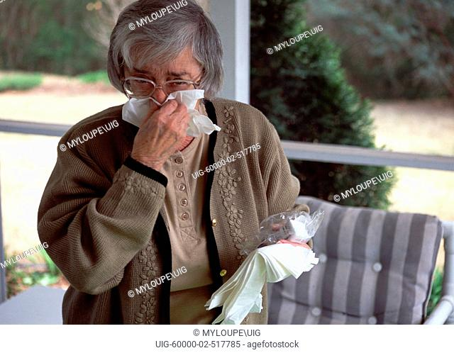 Elderly lady blowing nose