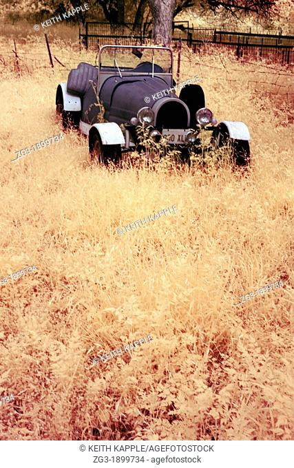 Infrared image of an Old Abandoned Rusty Vintage Convertible Car in a field of weeds out in West Texas