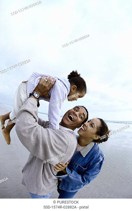 Parents with their daughter on the beach
