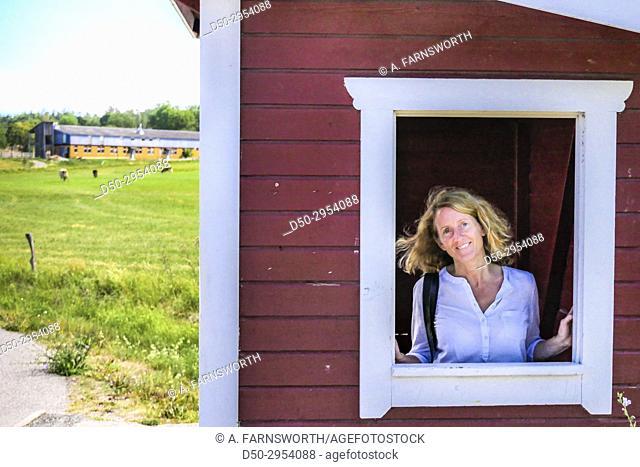 JÄRNA, SWEDEN Saltå Kvarn. Saltå mill and surrounding rural area with fields ecological food store. Portrait of woman at busstop